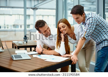 Young happy business people working at modern office - stock photo