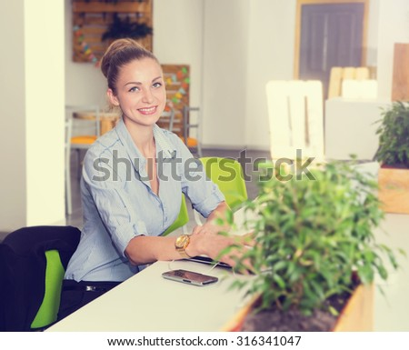 Young happy business woman - office staff. Female business. Woman working in the office. Female college students using laptop in computer class. Woman student working in a university laboratory.