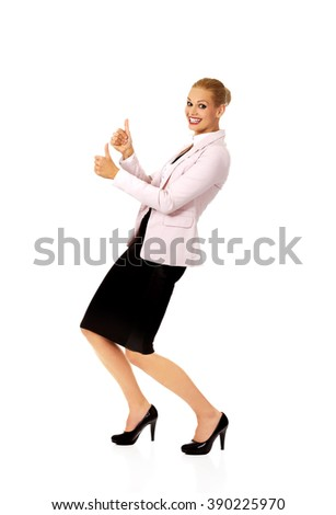 Young happy business woman shows thumbs up - stock photo