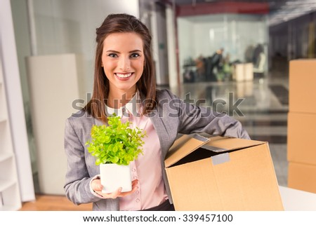 Young happy business woman with boxes for moving into a new office - stock photo