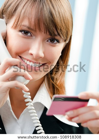 Young happy business woman with phone and credit card, at office - stock photo