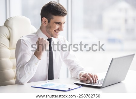 Young, happy businessman is working in his office. - stock photo