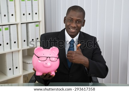 Young Happy Businessman Showing Thumb Up With Piggybank In Office - stock photo