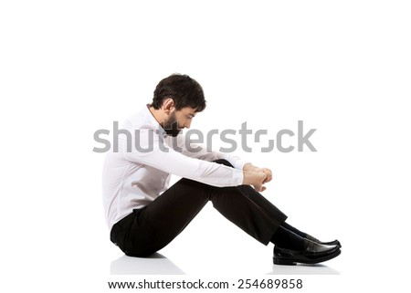 Young happy businessman sitting on the floor. - stock photo