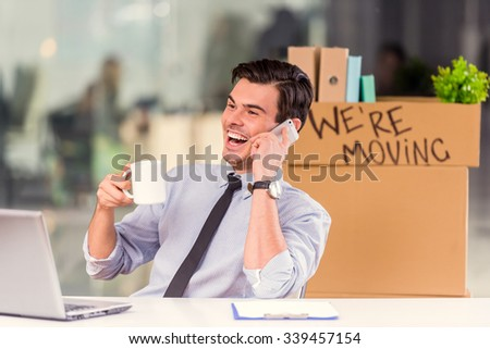 Young happy businessman with boxes to move to new office - stock photo