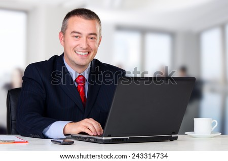Young happy businessman working in his office. - stock photo