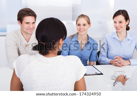 Young Happy Businesspeople Talking With Each Other In Office - stock photo