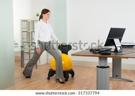 Young Happy Businesswoman Exercising With Pilates Ball On Chair In Office - stock photo