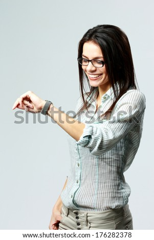 Young happy businesswoman looking at her watch on wrist on gray background - stock photo