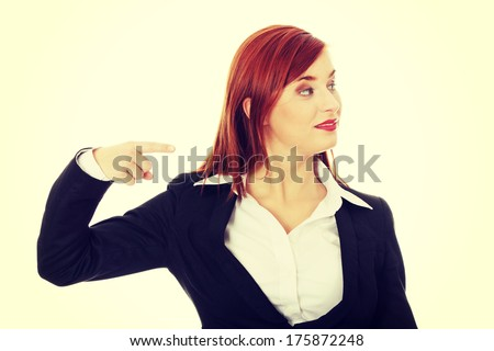 Young happy businesswoman pointing direction - stock photo