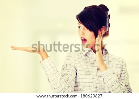 Young happy businesswoman presenting something on her hand