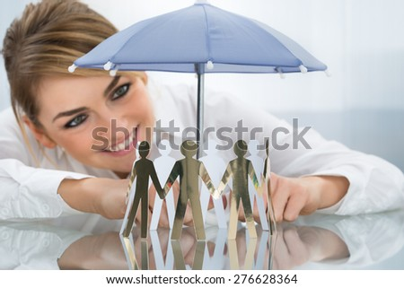Young Happy Businesswoman Protecting Cut-out Figures With Small Umbrella - stock photo