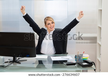 Young Happy Businesswoman Raising Hands In Office