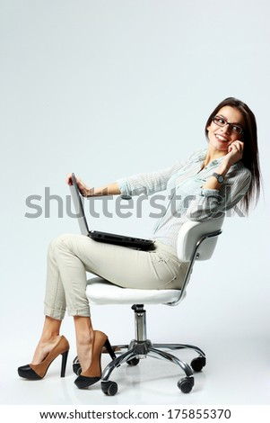 Young happy businesswoman sitting on the chair with laptop and talking on the phone on gray background - stock photo