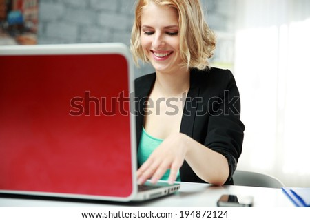Young happy businesswoman using laptop at office - stock photo