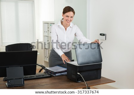 Young Happy Businesswoman Using Printer In Office - stock photo