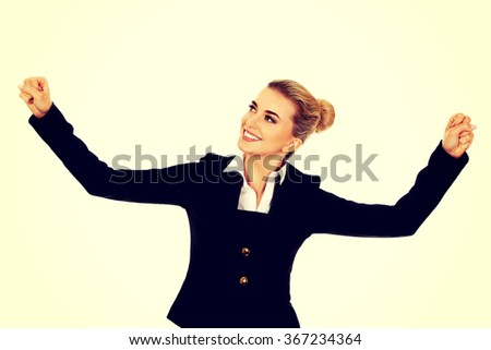 Young happy businesswoman with arms up. Winning concept - stock photo
