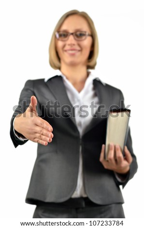 Young happy businesswoman with glasses gives a handshake holding a book. Isolated on white - stock photo