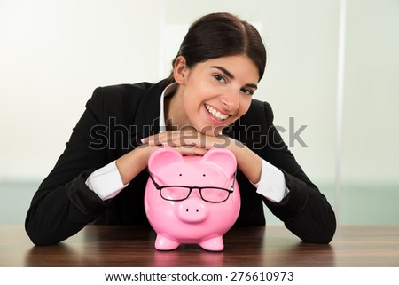 Young Happy Businesswoman With Pink Piggybank At Desk