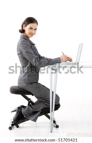 Young happy businesswoman working on kneeling chair, smiling, isolated on white.