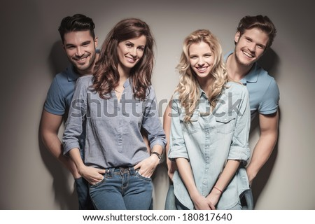 young happy casual women standing in front of their boyfriends in studio - stock photo