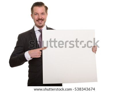 Young happy Caucasian businessman holding empty white board with copy space and pointing finger