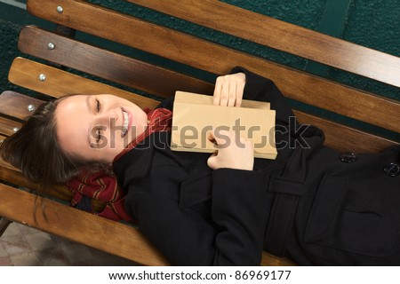 Young happy Caucasian woman lying on a bench reading a book (Selective Focus, Focus on the face)