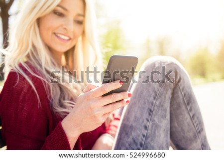 Young happy caucasian woman on the phone with her new smartphone at the park wearing casual clothes during a sunny day
