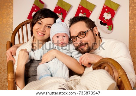 Young happy celebrate Chistmas at home - woman, man and newborn baby boy
