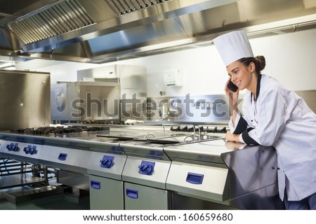 Young happy chef standing next to work surface phoning in professional kitchen - stock photo