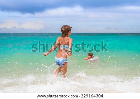 young happy child boy having fun in water, summer vacations on tropical beach - stock photo