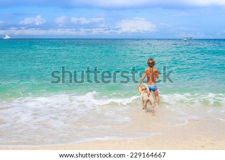 young happy child boy having fun with white dog in the sea, summer vacations