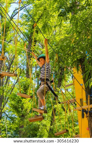 Young happy child boy in adventure park in safety equipment - stock photo
