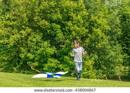 young happy child boy playing with bright kite in park. summer holiday vacation
