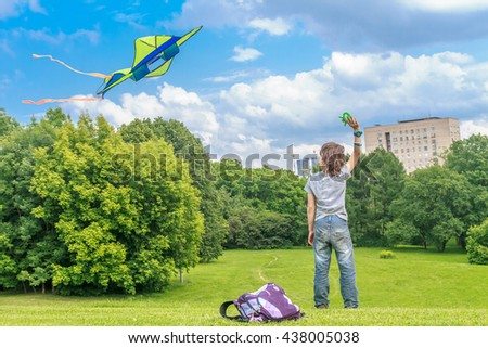 young happy child boy playing with bright kite in park. summer holiday vacation - stock photo