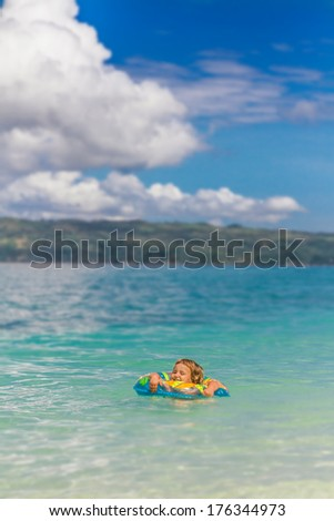 young happy child enjoying swimming on tropical beach