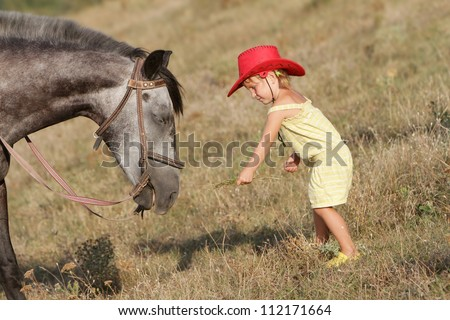 young happy child girl feeding horse on natural background - stock photo