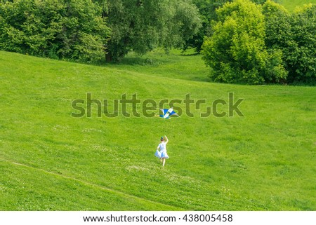 young happy child girl playing with bright kite in park. summer holiday vacation - stock photo