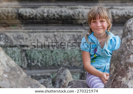 young happy child girl, smiling portrait, angkor wat, cambodia - stock photo