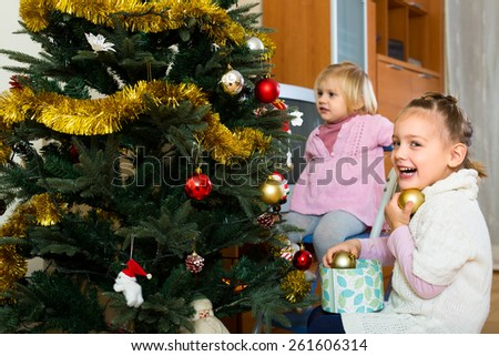 Young happy children decorating a christmas tree. One girl is looking at fir another is holding golden Christmas globes and smiling - stock photo