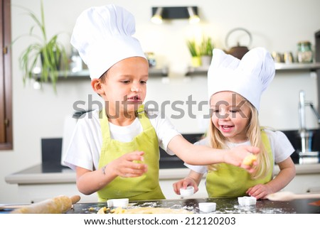 young happy children kids family having fun preparing a cake in kitchen at home