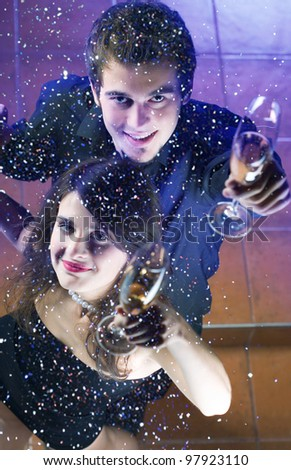 Young happy couple at celebration with glasses of champagne - stock photo