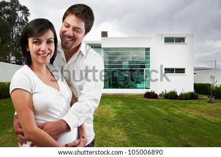 Young happy couple at their new big house