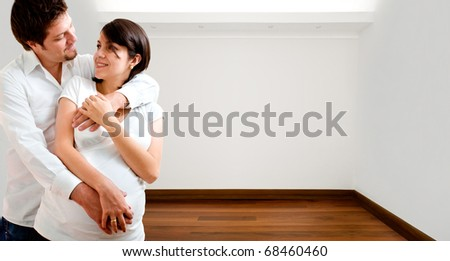 Young happy couple at their new empty apartment - stock photo