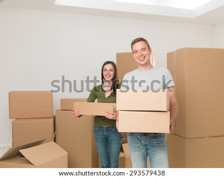 young happy couple carrying cardboard boxes, moving house - stock photo