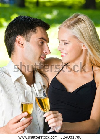 Young happy couple celebrating with champagne, outdoors. Love, flirt, romantic, relations, celebration theme concept.
