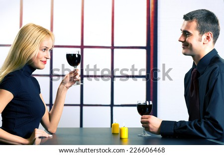 Young happy couple celebrating with red wine, indoors - stock photo