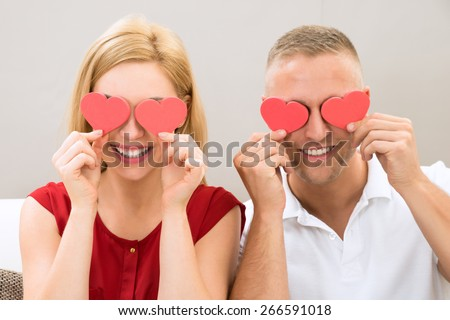 Young Happy Couple Covering Eyes With The Red Hearts - stock photo