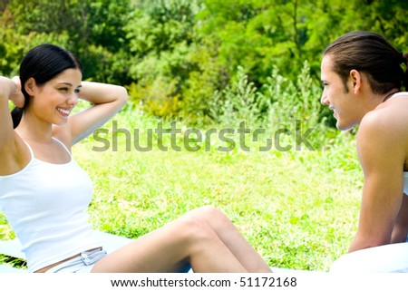 Young happy couple doing fitness exercises together outdoor