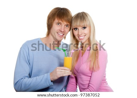Young happy couple drink orange juice, hold glass with straws, love smiling, wear sweater, looking at camera, isolated over white background - stock photo